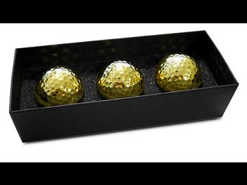 Einlochen wie ein Milliardär: Drei Golfbälle in luxuriöser Goldoptik.