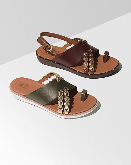 Two summer sandals placed on a light grey background.