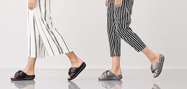 Two models wearing Loosh Luxe sequin Cross slide Sandals, shown in colours Silver and Black.