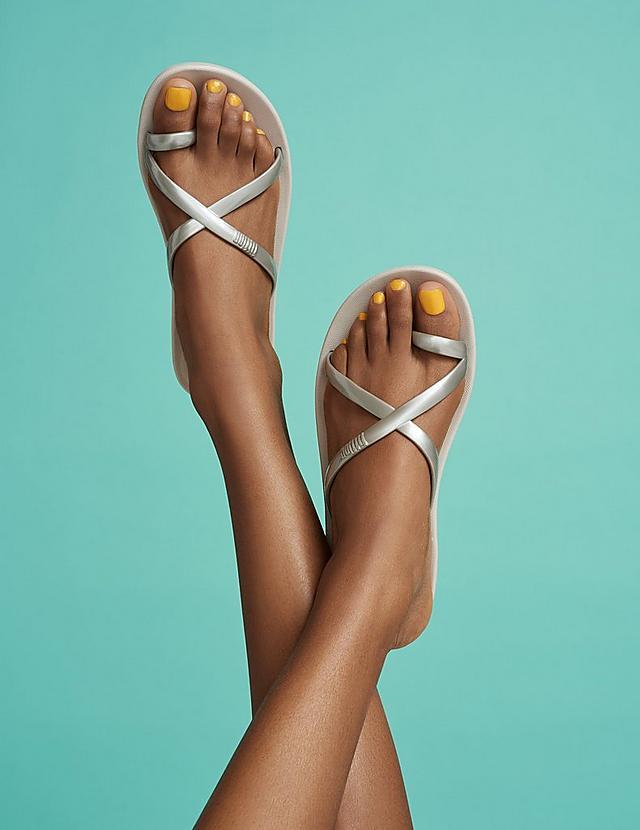 Women modelling Iqushion silver flip-flops