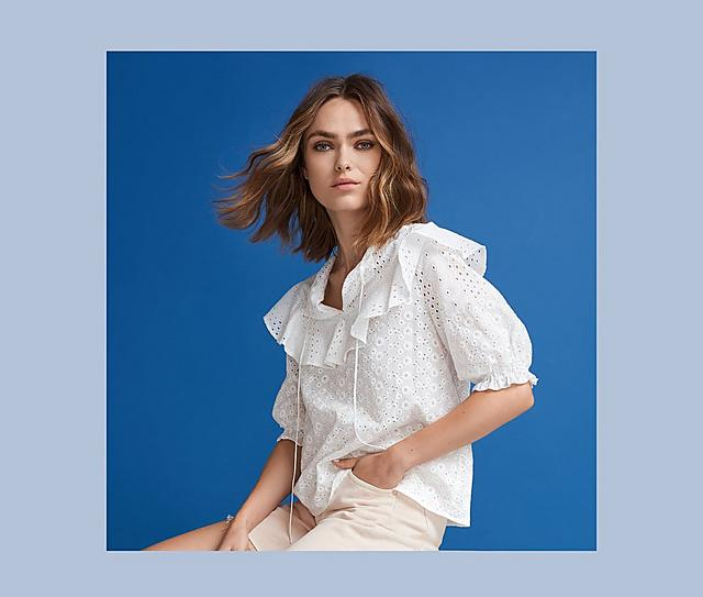 A woman wearing a white blouse on a blue background.