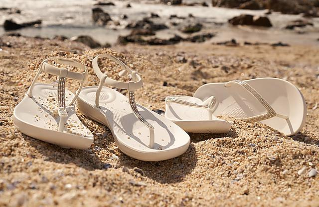 Fitflop Iqushion Flipflops in white with shimmer details on a beach.
