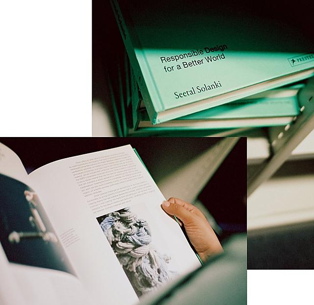 A woman is reading the page of a pastel green design book.