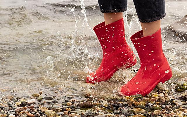 Lady jumping in water wearing Fitflop red wellington boots.