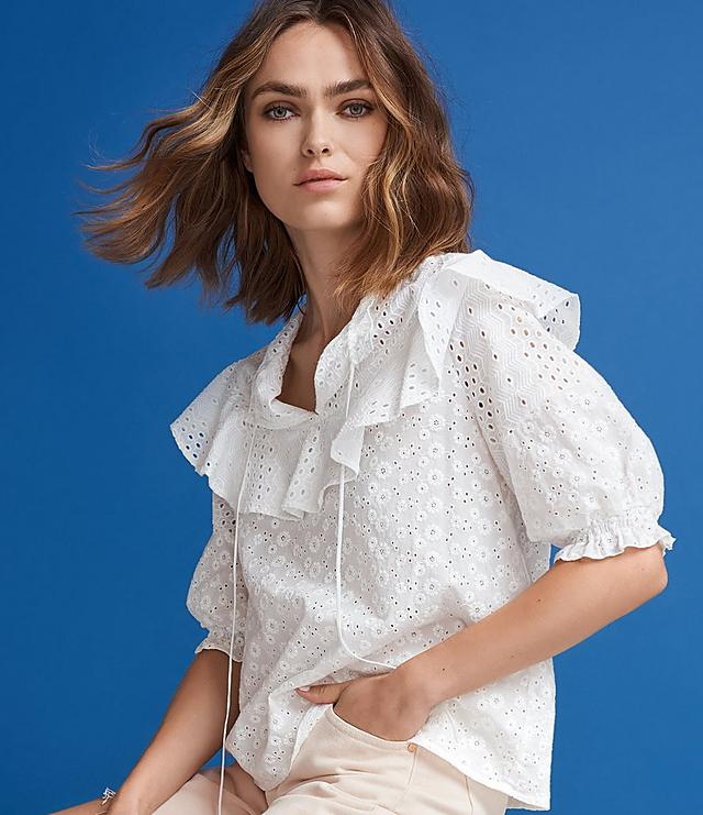 Woman wearing a white blouse on a blue background.
