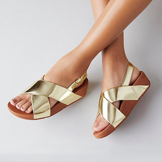 Fitflop Lulu gold slip-on sandals with cross over straps.