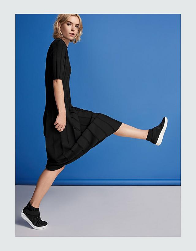 Women in black dress modelling Black slip-on high-top sneakers with white base.
