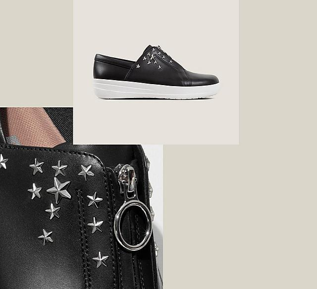 Black leather sneakers with silver star studs on the side and zip opening.