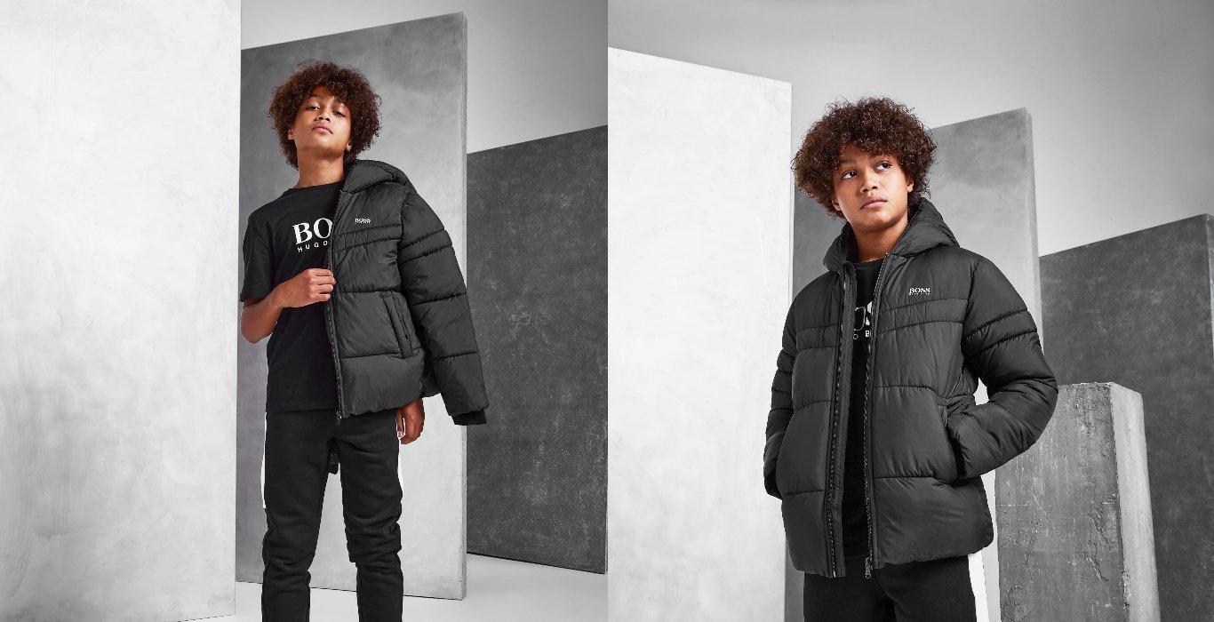 Två bilder på ett barn med en vadderad, svart jacka från BOSS Kids och svarta byxor
