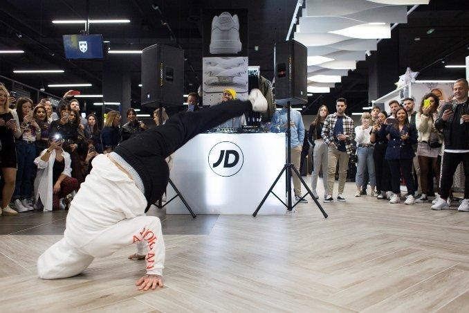 una persona haciendo breakdance en el suelo vestido de color blanco