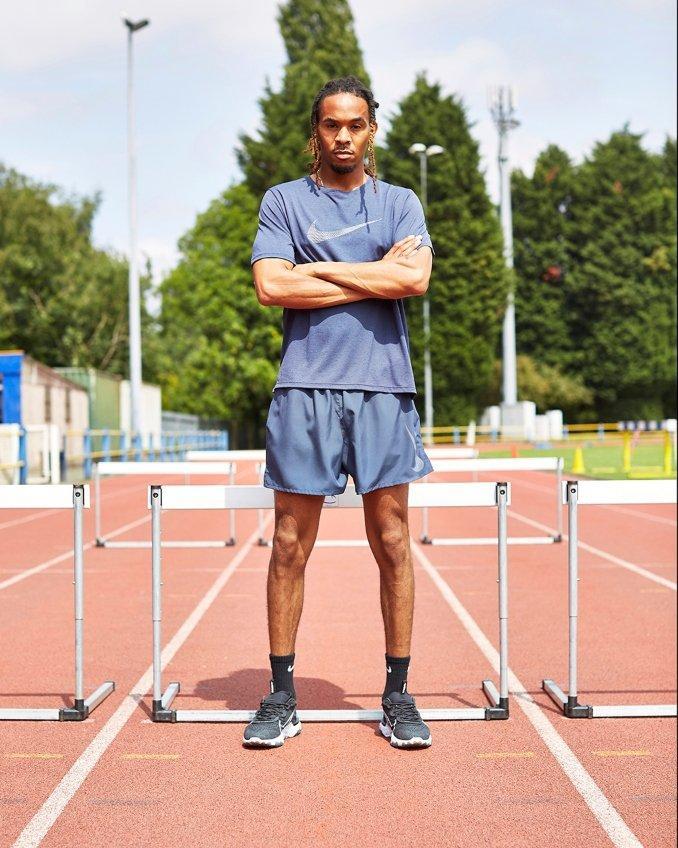Hombre con look deportivo en pista de atletismo