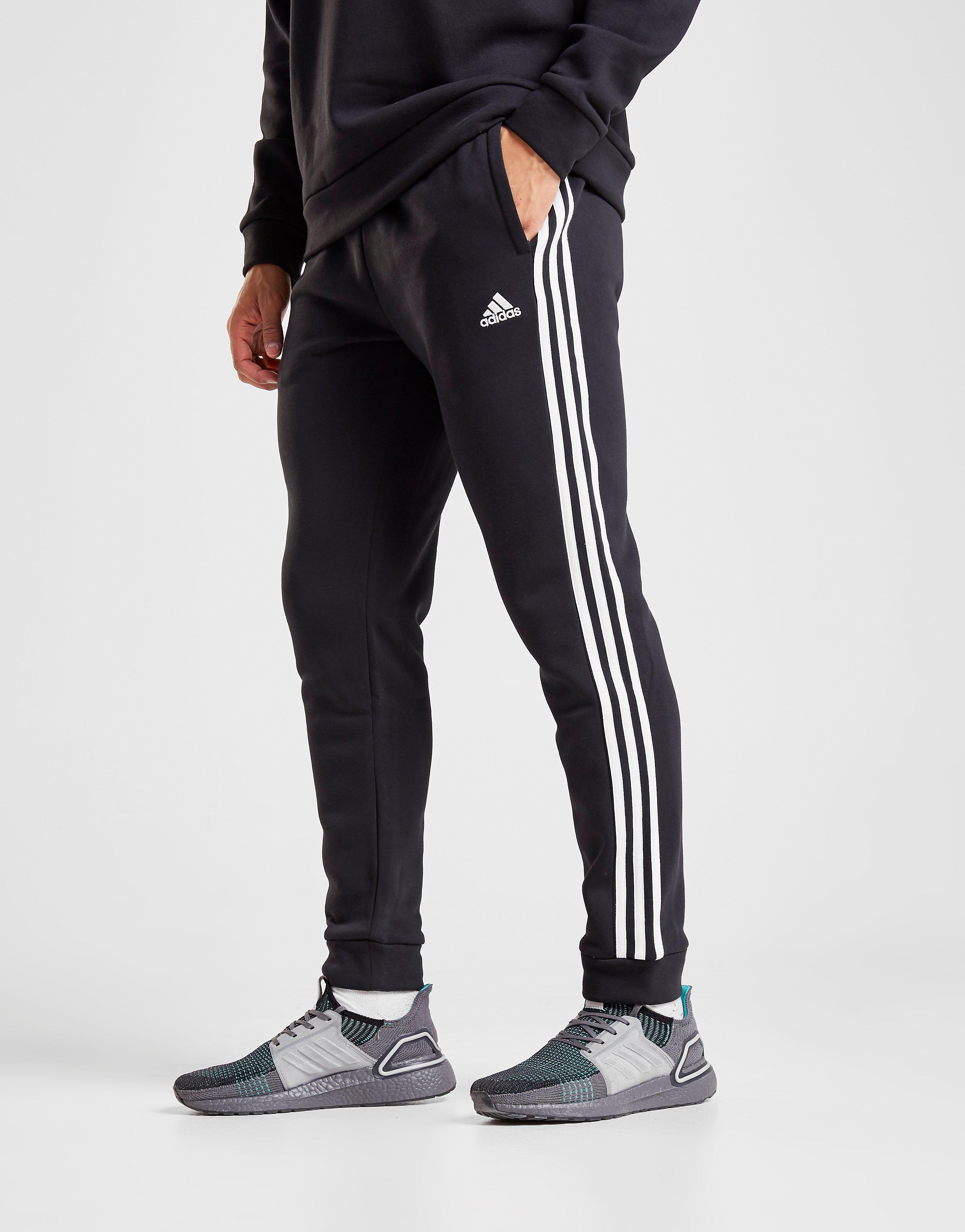 black adidas pants with white stripes