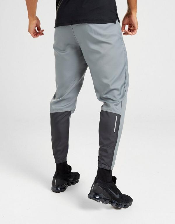 Costa internacional efectivo  Compra Nike pantalón de chándal Essential Woven Running en Gris